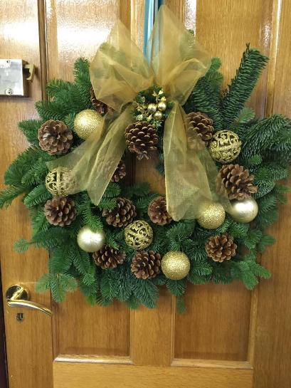 Gold Wreath on wooden door at kays flower school